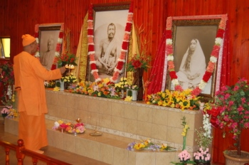 Swami Smarananandaji is waving 'arati' before the Holy Trio at the altar of the Shrine as a mark of inauguration